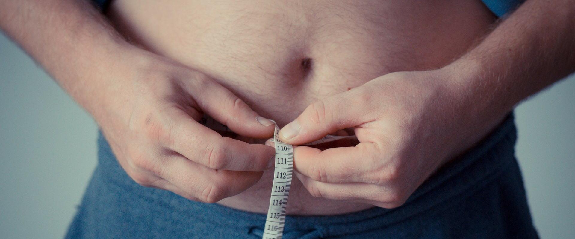 mężczyzna mierzący brzuch miarką