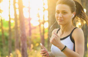 kobieta ze słuchawkami biegnąca przez las