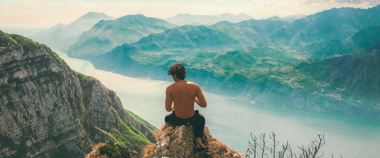 mężczyzna siedzący nad jeziorem w górach
